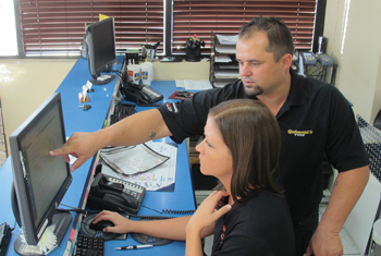 Manager Justin Essary and service advisor Stephanie Bunch consult over a pending tire order.