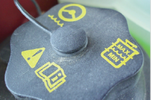 From the top in a clockwise direction, the icons on this power steering reservoir cap indicate power steering, fluid level and that the owner's manual should be consulted for the type of fluid required.