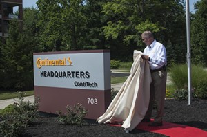 Jim Hill pulls away the sheet to unveil the new sign outside of ContiTech's Fairlawn headquarters.