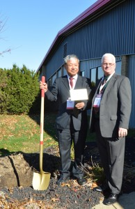 Jimmy Yang, Kenda USA president, plants a tree to celebrate the new tech center. Tom Williams (right), Kenda USA vice president of engineering, and Chairman Ying-Ming Yang also planted a tree.