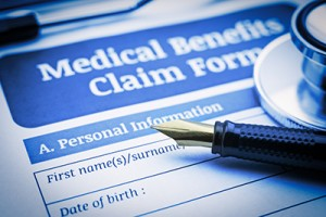 Fountain pen, a stethoscope and a medical benefit claim form.