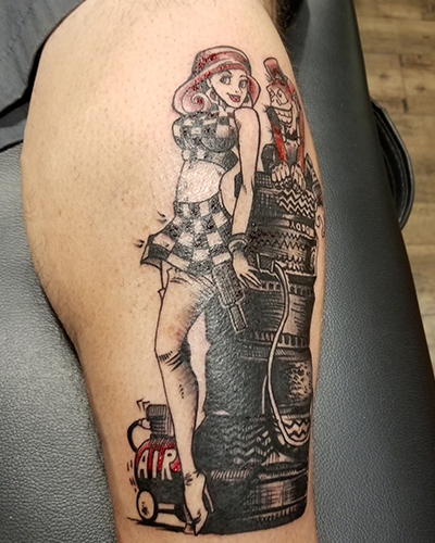 "bd47e569f A 12-in. by 4.5 in. design of a ""tire monkey"" on a stack of tires next to a  pin-up girl on Rivas' leg. ""I am a self-proclaimed tire monkey. [My tattoo]  ..."