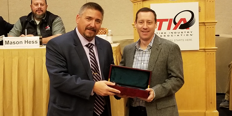 Tire Industry Association Outgoing President John Evankovich passes the gavel to incoming President Brian Rigney.