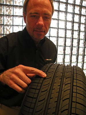 Hankook manager of tire development engineering Tom Kenny points to sipes, also called kerfs, that contribute to the snow, ice and wet traction of an OE all-season tread design.