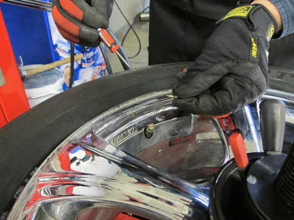 1: after positioning wheel assembly on tire changer, remove valve core. (note core in technicians fingers.)
