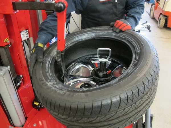 5: place tire on wheel and with a lever securely in place, twist the tire bead over the top rim flange by hand.